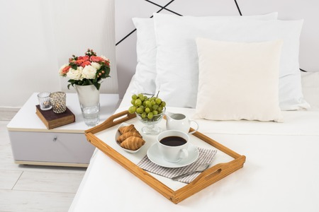 breakfast room: Breakfast in bed, tray with coffee, fruits and croissants on a bed with white linen in bedroom interior, hotel room