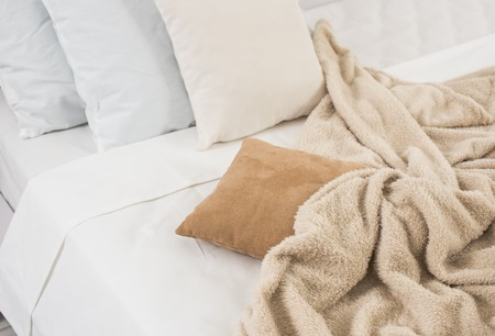 White and beige bedding, pillows and crumpled sheets, white linen cloth, abstract background.