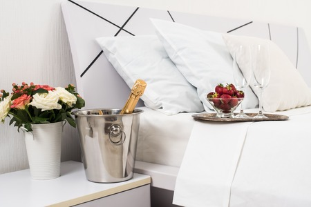 hotel room: Champagne in bed in a hotel room, ice bucket, glasses and fruits on white linen Stock Photo