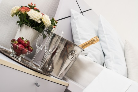 white linen: Champagne in bed in a hotel room, ice bucket, glasses and fruits on white linen Stock Photo