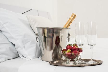 caras emociones: Champagne en la cama en una habitación de hotel, cubo de hielo, vasos y frutas en lino blanco