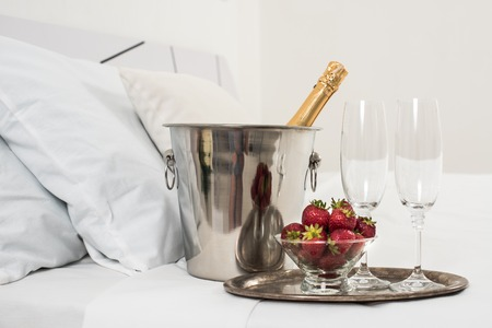 Champagne in bed in a hotel room, ice bucket, glasses and fruits on white linen Stock fotó