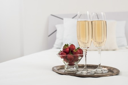 champagne bottle: Champagne in bed in a hotel room, ice bucket, glasses and fruits on white linen Stock Photo