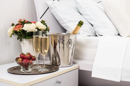 Champagne en la cama en una habitación de hotel, cubo de hielo, vasos y frutas en lino blanco