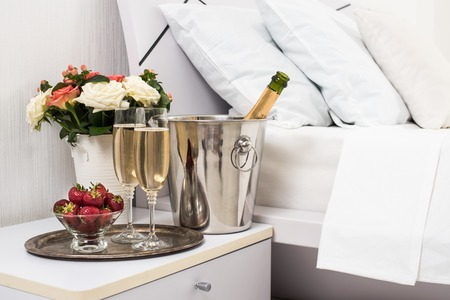 hotel: Champagne in bed in a hotel room, ice bucket, glasses and fruits on white linen Stock Photo