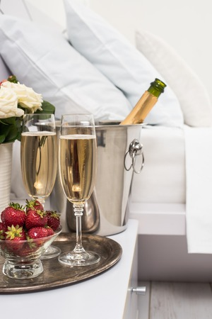 샴페인 호텔 방, 얼음 양동이, 안경 및 과일 화이트 린 넨에 침대에서