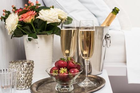 흰색 리넨에 호텔 방, 얼음 양동이, 안경 및 과일 침대에서 샴페인 스톡 콘텐츠