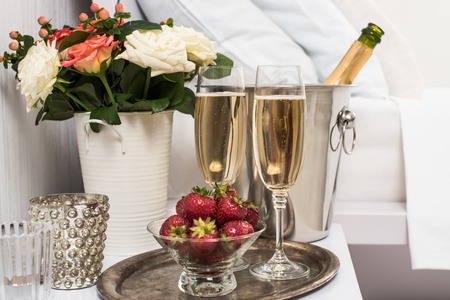 Champagne in bed in a hotel room, ice bucket, glasses and fruits on white linen Stock Photo