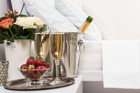 ホテルの部屋でベッドのシャンパン氷バケット、メガネ、白いリネンのフルーツ 写真素材
