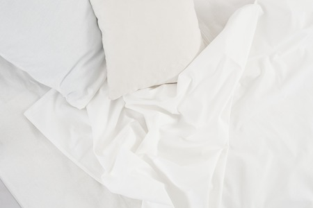tela blanca: New snow-white bed, pillows and crumpled sheets, white linen cloth, white abstract background.