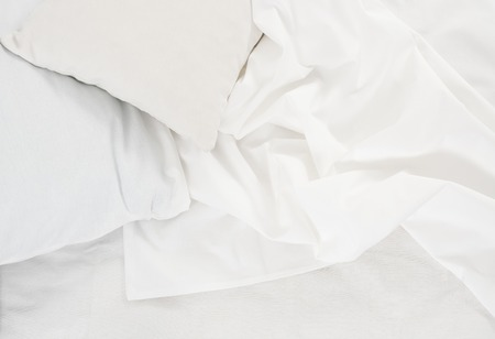 bed sheet: New snow-white bed, pillows and crumpled sheets, white linen cloth, white abstract background.