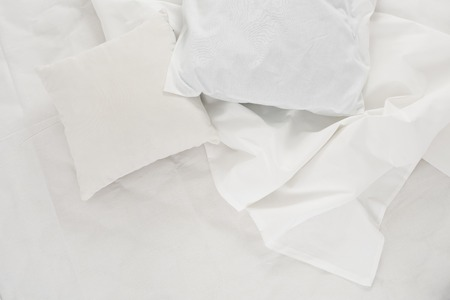 white linen: New snow-white bed, pillows and crumpled sheets, white linen cloth, white abstract background.
