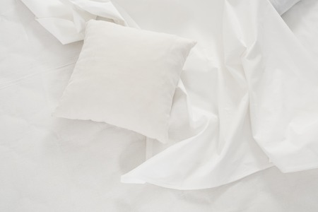 white pillow: New snow-white bed, pillows and crumpled sheets, white linen cloth, white abstract background.