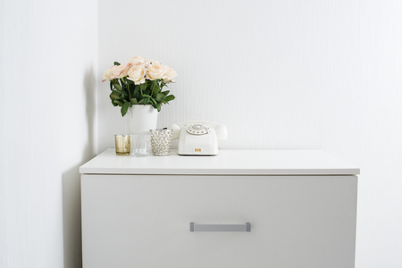 arrangements: Modern interior decor with vintage details: white rotary phone and fresh flowers on a table. Clean white room in real apartment. Stock Photo
