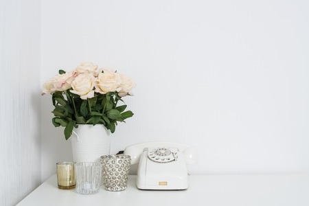 Modern interior decor with vintage details: white rotary phone and fresh flowers on a table. Clean white room in real apartment. Foto de archivo