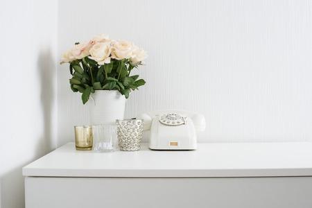 Modern interieur met uitstekende informatie: wit roterende telefoon en verse bloemen op een tafel. Schone witte kamer in real appartement.