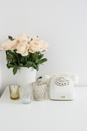 white interior: Modern interior decor with vintage details: white rotary phone and fresh flowers on a table. Clean white room in real apartment. Stock Photo