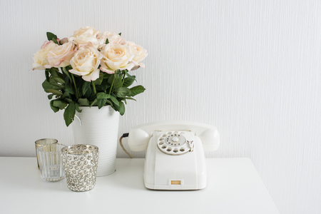 flower arrangement: Modern interior decor with vintage details: white rotary phone and fresh flowers on a table. Clean white room in real apartment. Stock Photo