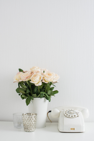 Modern interior decor with vintage details: white rotary phone and fresh flowers on a table. Clean white room in real apartment. Stock Photo