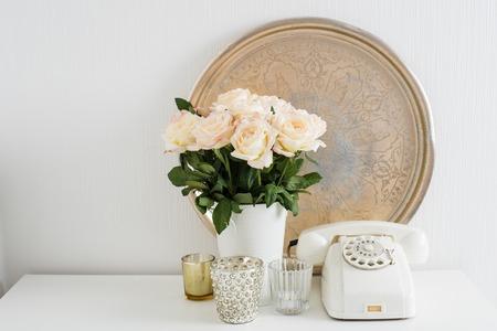 Vintage interieurdecoratie: witte roterende telefoon, zilveren dienblad, kaarsen en rozen op een tafel. Retro-stijl van de flatdecoratie, close-up.
