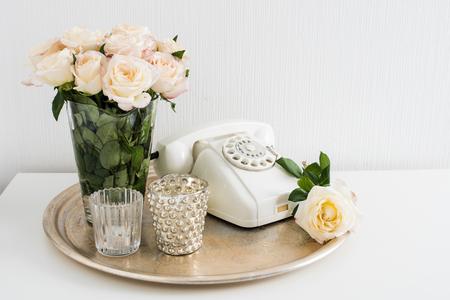 arreglo floral: Vintage decoración interior de una casa: teléfono de disco blanco, bandeja de plata, velas y rosas en una mesa. Apartamento decoración de estilo retro, primer plano. Foto de archivo