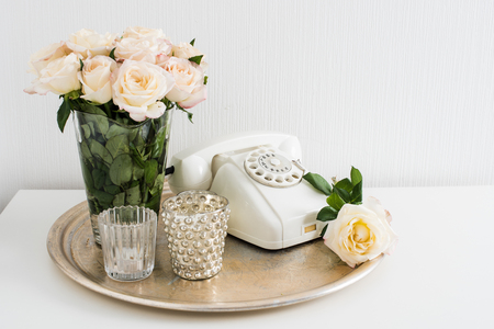 flower arrangement: Vintage home interior decoration: white rotary phone, silver tray, candles and roses on a table. Apartment decoration retro style, closeup. Stock Photo