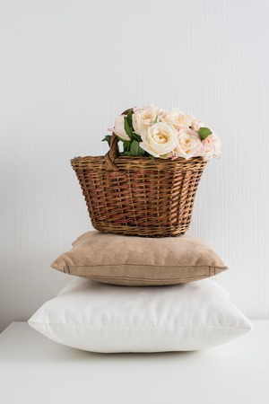 wall decor: Basket with flowers on a pile of pillows by the white wall, a cozy home decor