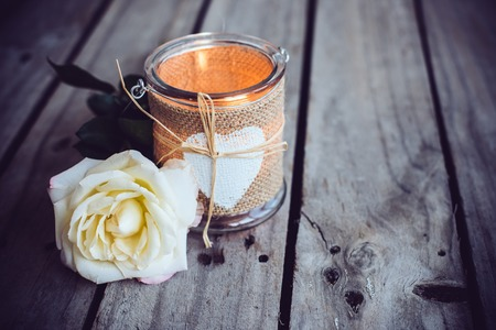 Burning candle in a decorative jar and flower of rose on old wooden board. Rustic decor.