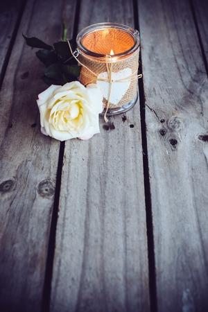 bougie coeur: Bougie allumée dans un pot décoratif et fleur de rose sur la vieille planche de bois. Décor rustique.