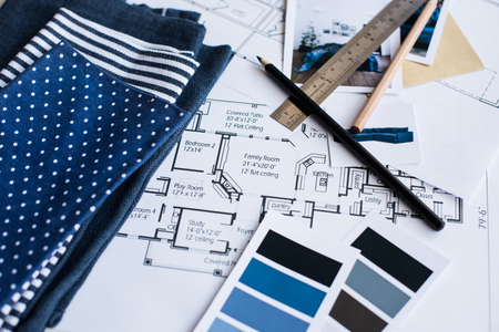 Inter ontwerper werktafel, een architecturaal plan van het huis, een kleurenpalet, meubilair en stofstalen in blauwe kleur. Tekeningen en plannen voor huisdecoratie.