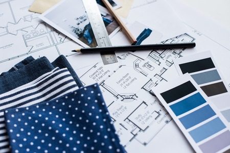 Interior designer's working table, an architectural plan of the house, a color palette, furniture and fabric samples in blue color. Drawings and plans for house decoration. 免版税图像