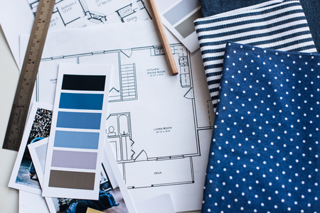 paint tool: Interior designers working table, an architectural plan of the house, a color palette, furniture and fabric samples in blue color. Drawings and plans for house decoration.