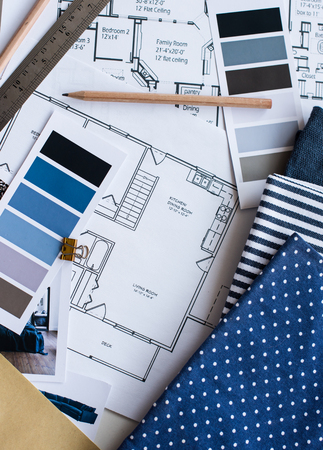 painting and decorating: Interior designers working table, an architectural plan of the house, a color palette, furniture and fabric samples in blue color. Drawings and plans for house decoration.
