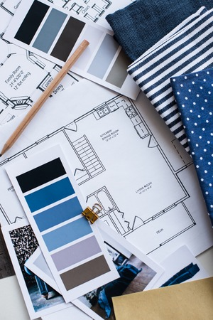 the designer: Interior designers working table, an architectural plan of the house, a color palette, furniture and fabric samples in blue color. Drawings and plans for house decoration.