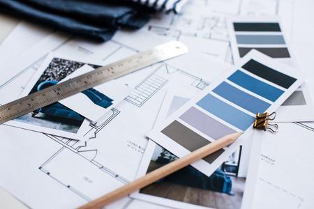 Inter Designer-Arbeitstisch, ein Architekturplan des Hauses, eine Farbpalette, Möbel und Stoffmuster in blauer Farbe. Zeichnungen und Pläne für Hausdekoration.
