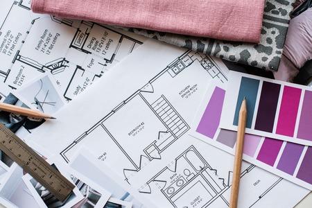 デザイナーの作業テーブル、家の建築計画、グレーとピンク色のカラー パレット、家具、生地サンプルを間します。図面および家の装飾のための計
