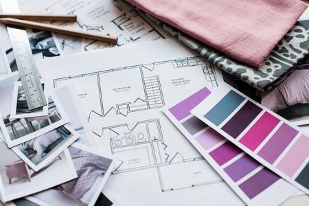Werktafel interieur ontwerper, een bouwkundig plan van het huis, een kleurenpalet, meubilair en stofstalen in grijs en roze kleur. Tekeningen en plannen voor huisdecoratie.