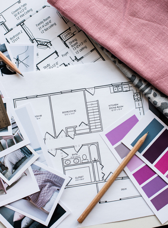 grey house: Interior designers working table, an architectural plan of the house, a color palette, furniture and fabric samples in grey and pink color. Drawings and plans for house decoration.