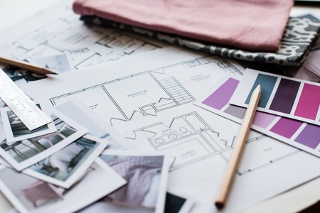 Interior designer's working table, an architectural plan of the house, a color palette, furniture and fabric samples in grey and pink color. Drawings and plans for house decoration. Imagens - 44932217