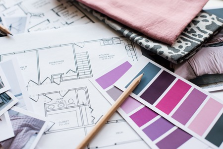 Interior designer's working table, an architectural plan of the house, a color palette, furniture and fabric samples in grey and pink color. Drawings and plans for house decoration. Foto de archivo