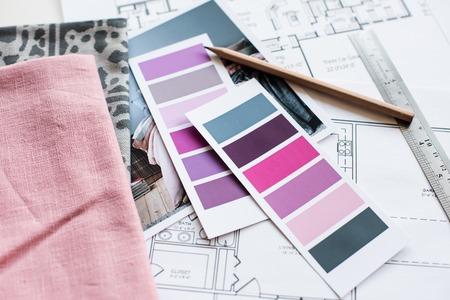 Inter Designer-Arbeitstisch, ein Architekturplan des Hauses, eine Farbpalette, Möbel und Stoffmuster in grau und rosa Farbe. Zeichnungen und Pläne für Hausdekoration. Lizenzfreie Bilder
