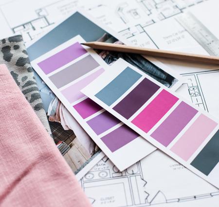 Arbeitstisch Innenarchitekt, ein Architekturplan des Hauses, eine Farbpalette, Möbel und Stoffmuster in grau und rosa Farbe. Zeichnungen und Plänen für Hausdekoration.