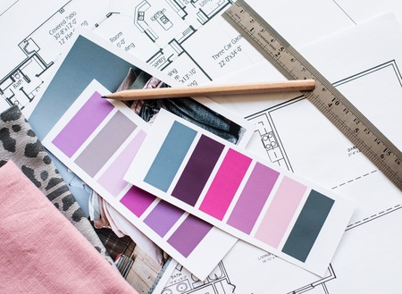 Interior designer's working table, an architectural plan of the house, a color palette, furniture and fabric samples in grey and pink color. Drawings and plans for house decoration. 免版税图像