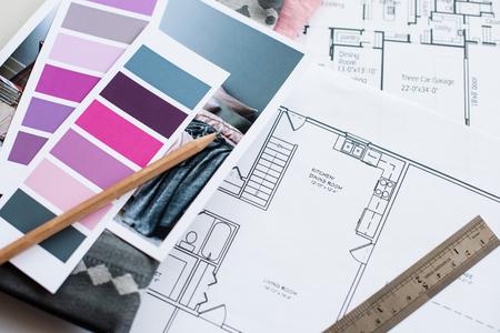 De werktafel van de interieurontwerper, een bouwkundig plan van het huis, een kleurenpallet, meubels en stofstalen in grijs en roze kleur. Tekeningen en plannen voor huisdecoratie.