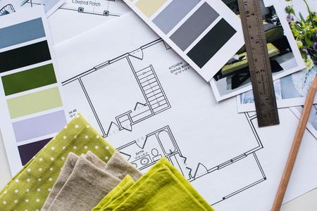La table de designer d'intérieur de travail, un plan architectural de la maison, une palette de couleurs, du mobilier et des échantillons de tissu de couleur jaune et gris. Dessins et plans de décoration de la maison.