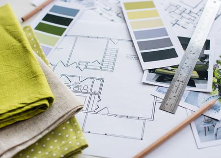 la mesa de diseñador Inter de trabajo, un plan arquitectónico de la casa, una paleta de colores, muebles y muestras de tela de color amarillo y gris. Dibujos y planos para la decoración de la casa. Foto de archivo