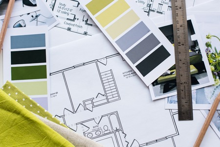 grey house: Interior designers working table, an architectural plan of the house, a color palette, furniture and fabric samples in yellow and grey color. Drawings and plans for house decoration.