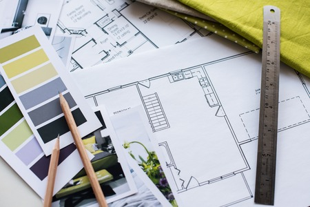 Werktafel interieur ontwerper, een bouwkundig plan van het huis, een kleurenpalet, meubilair en stofstalen in gele en grijze kleur. Tekeningen en plannen voor huisdecoratie.