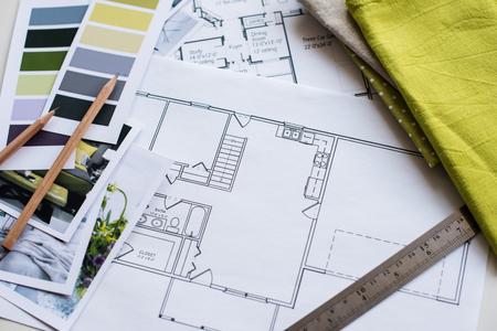 デザイナーの作業テーブル、家の建築計画、黄色とグレー色のカラー パレット、家具、生地サンプルを間します。図面および家の装飾のための計画
