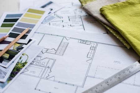 design interior: Interior designers working table, an architectural plan of the house, a color palette, furniture and fabric samples in yellow and grey color. Drawings and plans for house decoration.